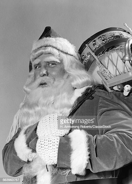 1940s PORTRAIT OF SMILING SANTA CLAUS WITH A SACK FOR OF TOY PRESENTS SLUNG OVER HIS SHOULDER LOOKING AT CAMERA
