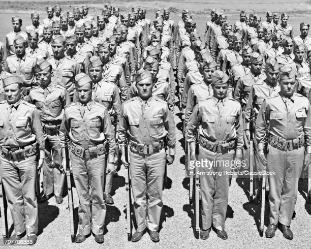 1940s ROWS OF AMERICAN WORLD WAR II SOLDIERS STANDING AT ATTENTION WITH RIFLES