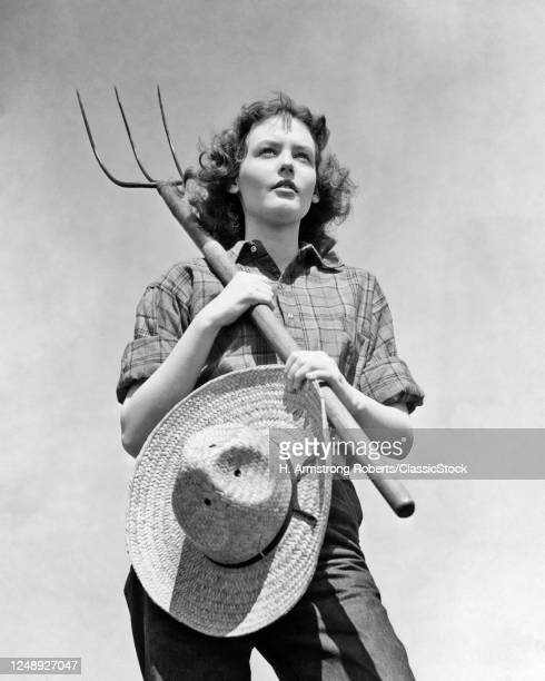 1940s Rural Farmer Plaid Shirt And Jeans Holding Hay Fork And Straw Hat Paused Standing Looking Off Into The Future Worried