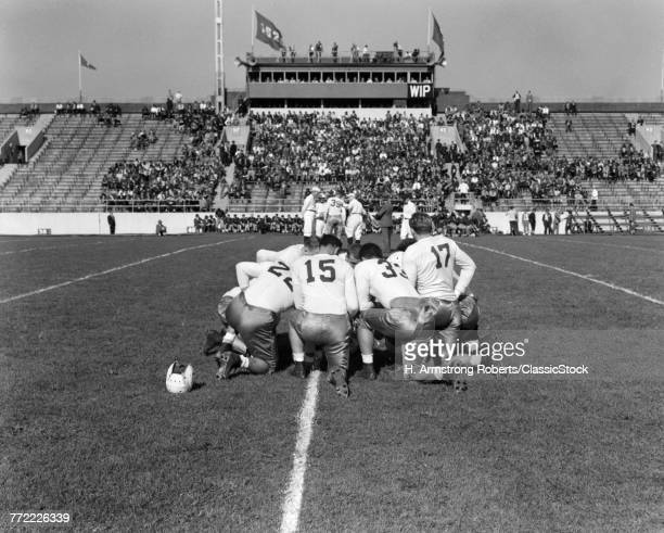 1940s SCHOOL FOOTBALL PLAYERS IN KNEELING HUDDLE ON FIELD