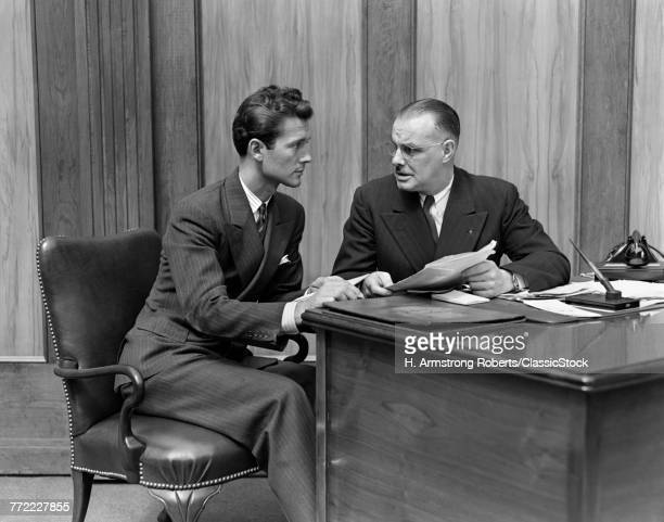 1940s SENIOR AND JUNIOR BUSINESS MEN WORKING TOGETHER IN OFFICE SITTING AT DESK REVIEWING A CONTRACT