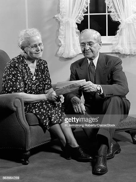 1940s SENIOR COUPLE READING MAIL TOGETHER IN LIVING ROOM HUSBAND WIFE INDOOR