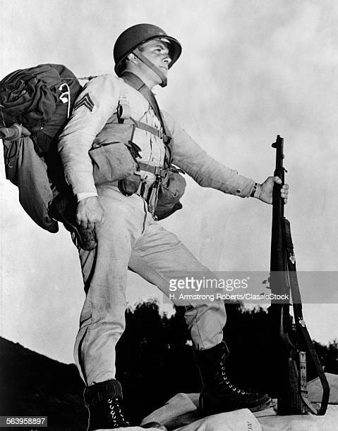 1940s SERGEANT IN US ARMY UNIFORM IN PROFILE POSING WITH M1 GARAND RIFLE HELMET BACKPACK AND BOOTS