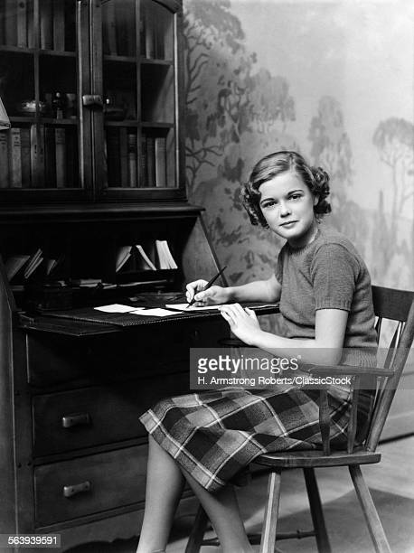 1940s SERIOUS TEENAGE GIRL SITTING AT DESK LOOKING AT CAMERA WRITING A LETTER