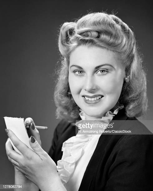 1940s Smiling Blond Woman With Very Big Victory Rolls Hair Style Ruffle Shirt Looking At Camera Writing On Notepad With Pencil