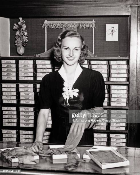 1940s smiling woman sales clerk behind hosiery department counter of store looking at camera hand inside sheer stocking