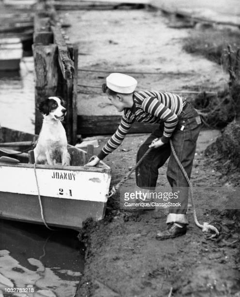 1940s TEENAGE BOY WEARING SAILOR HAT STRIPED SHIRT BLUE JEANS LANDING ROW BOAT CARRYING PET DOG