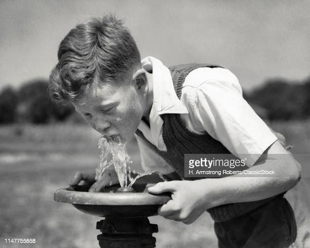 1940s THIRSTY BOY WITH FRECKLES DRINKING FROM PUBLIC WATER FOUNTAIN IN MUNICIPAL CITY PARK