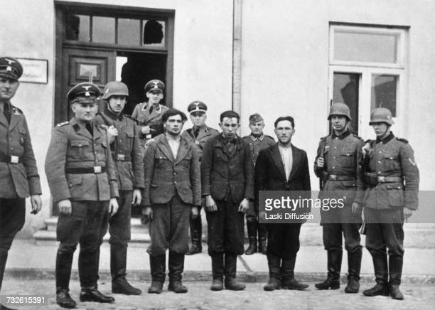 Three prisoners who have been condemned to death with German military personnel outside a military court in Kutno in Germanoccupied Poland circa 1942...