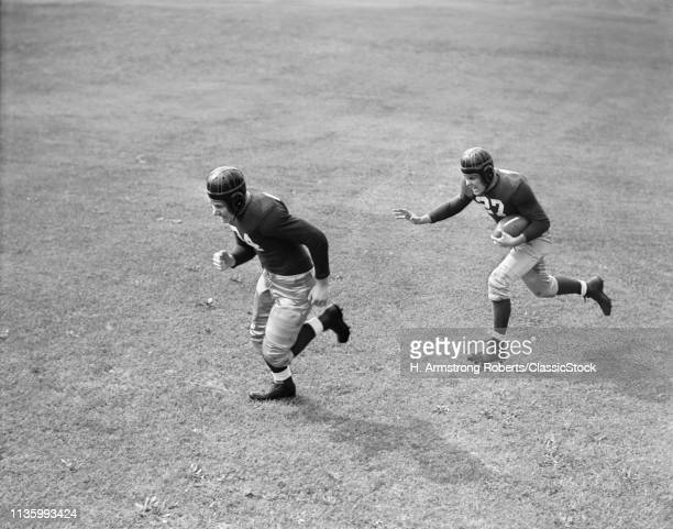1940s TWO MEN PLAYING FOOTBALL WEARING LEATHER HELMETS ONE RUNNING WITH FOOTBALL OTHER BLOCKING FOR HIM