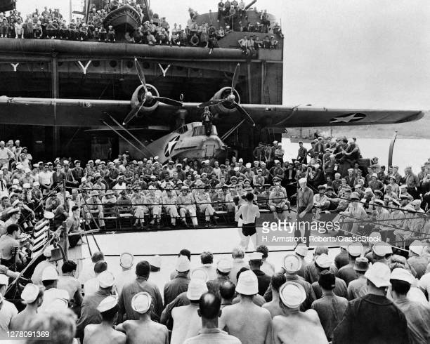 1940s Us Navy Sailors And Officers Watching A Boxing Match Bout Aboard Ww2 Aircraft Carrier Pby Catalina Flying Boat In B/G