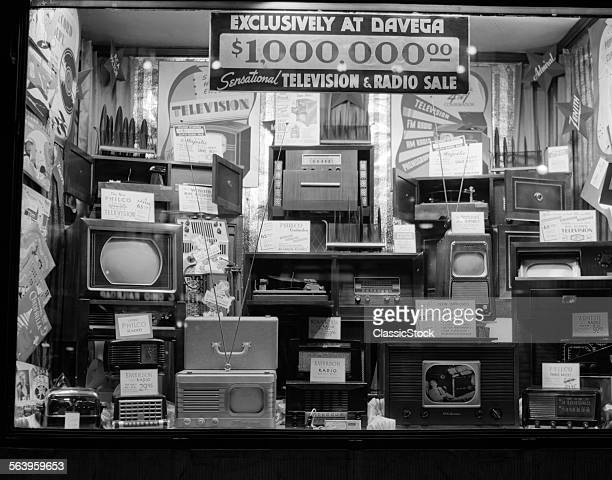 1940s WINDOW OF STORE SELLING RADIOS AND TELEVISIONS ADVERTISING A MILLION DOLLAR SALE