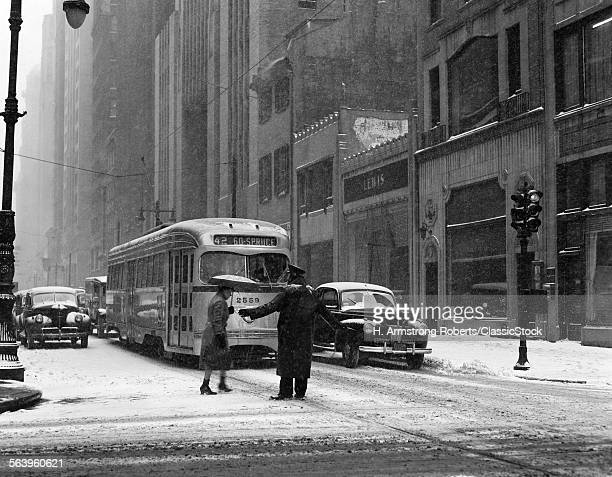 1940s WINTER STREET SCENE ANONYMOUS POLICEMAN HELPING WOMAN CROSS SNOWY STREET PAST WAITING TROLLEY CAR AND AUTOMOBILES