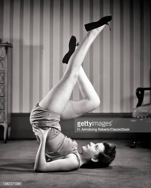 1940s Woman Lying On Back On Floor Doing Exercise Legs In The Air Doing Bicycle Movements