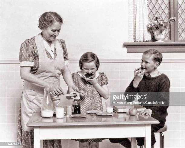 1940s woman making bread and jelly glasses of milk and an apple in the kitchen for boy and girl as after school snacks