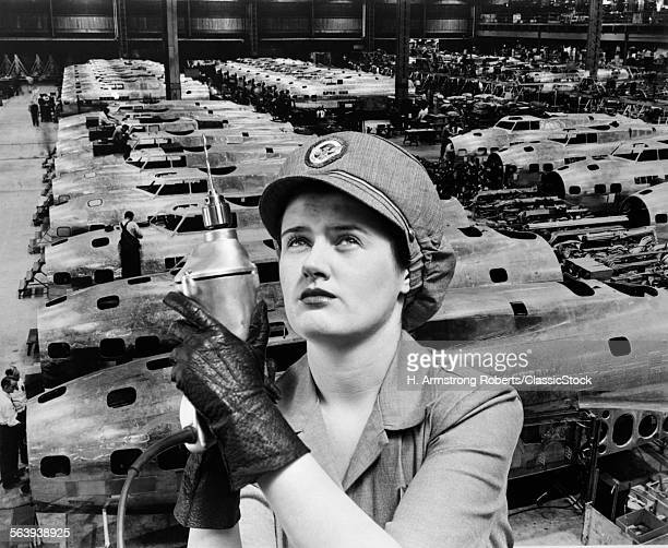 1940s WOMAN ROSIE THE RIVETER SUPERIMPOSED OVER AIRPLANES IN FACTORY 1940s WARTIME WWII
