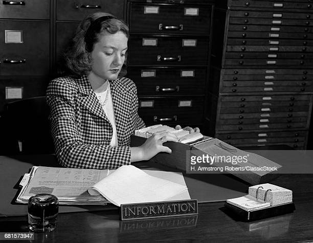 1940s WOMAN SEATED AT...