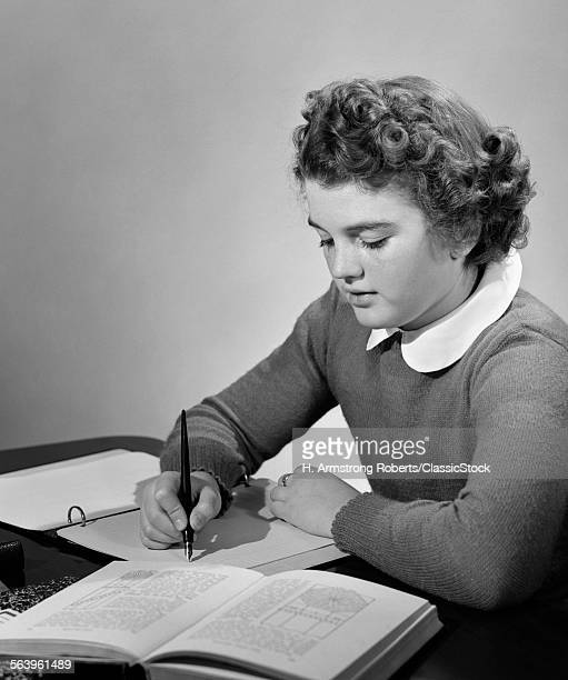 1940s YOUNG GIRL IN SCHOOL UNIFORM STUDYING AT DESK WITH BOOKS AND NOTES