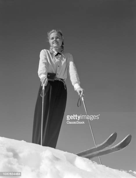 1940s SMILING BLOND WOMAN SKIER POISED ON HILL TOP TO BEGIN DOWNHILL SKIING WINTER OUTDOOR