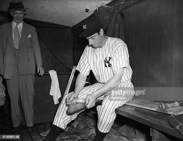 Star Yankee outfielder Joe DiMaggio preparing his bat for a game