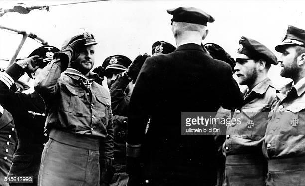 1913 1941UBoot Kommandant Dwird zusammen mit seiner Besatzung nacherfolgreicher Feindfahrt durch VizeadmiralDönitz ausgezeichnetOktober 1940
