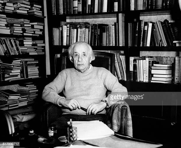 Albert Einstein famed theoretical physicist seated in front of bookcase.