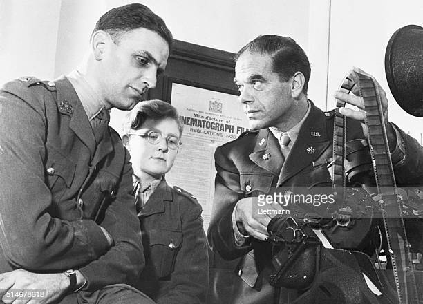 Colonel Frank Capra US Army Signal Corps right consults Major Hugh Stewart left Officer Commanding Army Unit about the first official film record...