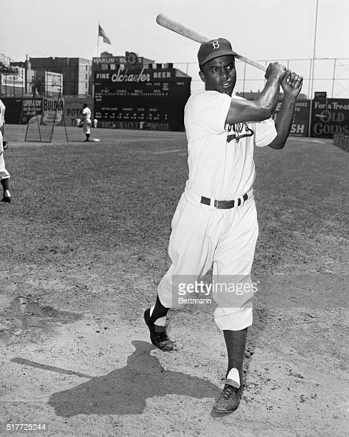 Jackie Robinson during baseball practice. J. Robinson shown bending to catch a ground ball. ACME