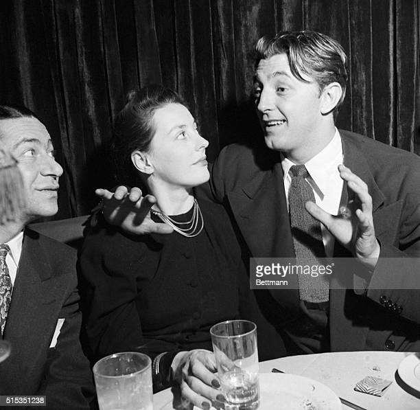1950New York New York Actor Robert Mitchum is shoen with his arm around his wife at the El Morroco Club They are seated and talking to another man at...