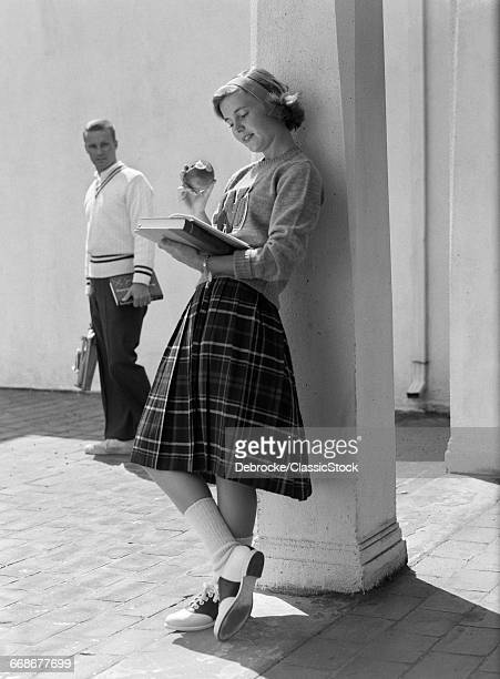 1950s 1960s BLOND TEEN SCHOOL GIRL PLAID SKIRT LEANING AGAINST COLUMN EATING APPLE READING BOOK AS BOY WALKS BY LOOKING AT HER