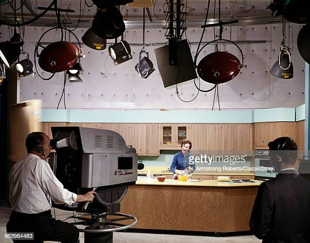 1950s 1960s CAMERA MAN AND DIRECTOR IN STUDIO KITCHEN SET SHOOTING WOMAN PERFORMING COOKING SHOW FOR TELEVISION PROGRAM