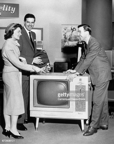 1950s 1960s COUPLE BUYING NEW CONSOLE TELEVISION FROM APPLIANCE SALESMAN