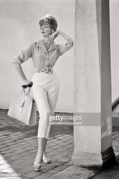 1950s 1960s FULL LENGTH PORTRAIT WOMAN WEARING BUTTON DOWN SHIRT CAPRI PANTS HOLDING STRAW BAG SUNGLASSES POSING BY COLUMN