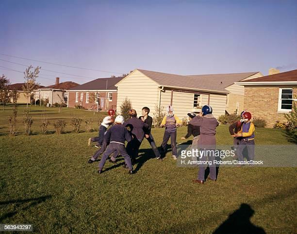 1950s 1960s GROUP NEIGHBORHOOD BOYS PLAY TOUCH FOOTBALL BACKYARD SUBURBAN HOUSES