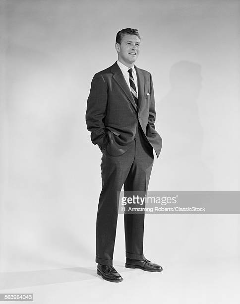 1950s 1960s PORTRAIT SMILING MAN STANDING WITH HANDS IN POCKETS WEARING SUIT AND TIE