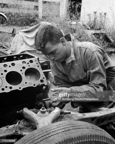 1950s 1960s TEEN IN OVERALLS WORKING UNDER HOOD OF HOT ROD