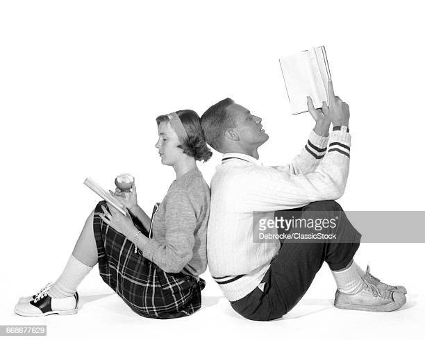 1950s 1960s TEENAGE HIGH SCHOOL COUPLE BOY GIRL STUDENTS LEANING BACK TO BACK DATING STUDYING READING BOOKS TOGETHER