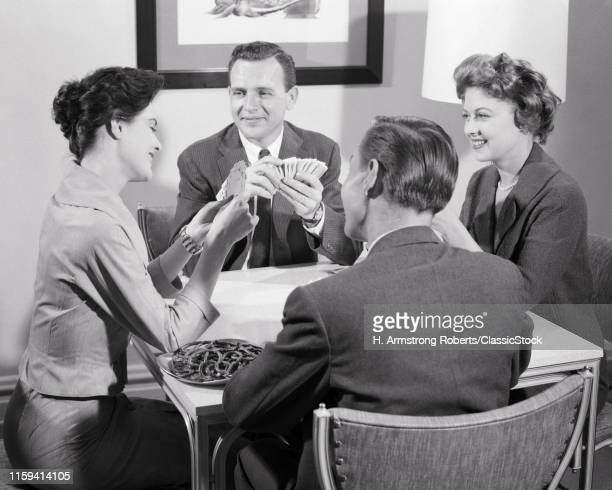 1950s 1960s TWO COUPLES SITTING AT TABLE PLAYING A GAME OF CARDS