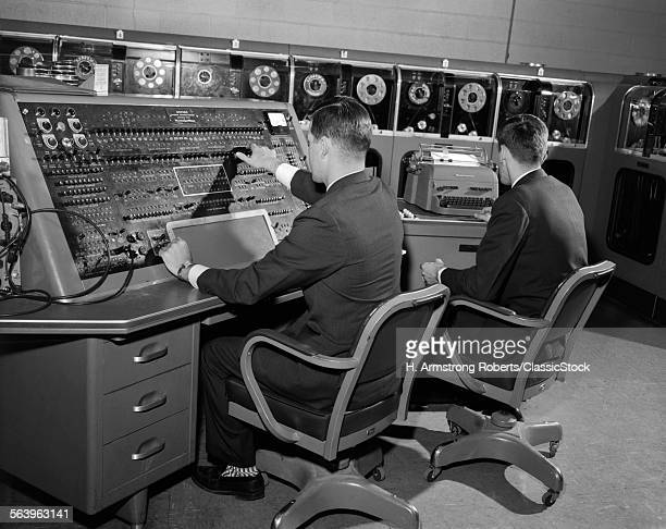 1950s 1960s UNIVAC COMPUTER ROOM WITH TWO MEN WORKING AT CONSOLE AND TYPEWRITER KEYBOARD