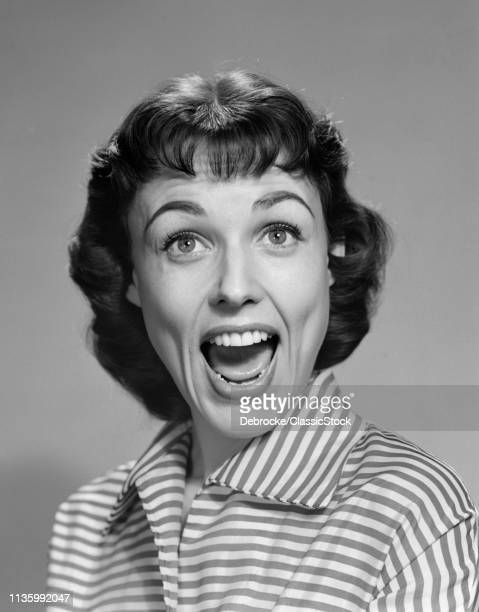 1950s 1960s WOMAN BRUNETTE SMILING LAUGHING MOUTH OPEN WIDE HAPPY FUNNY FACE LOOKING AT CAMERA WEARING STRIPED BLOUSE