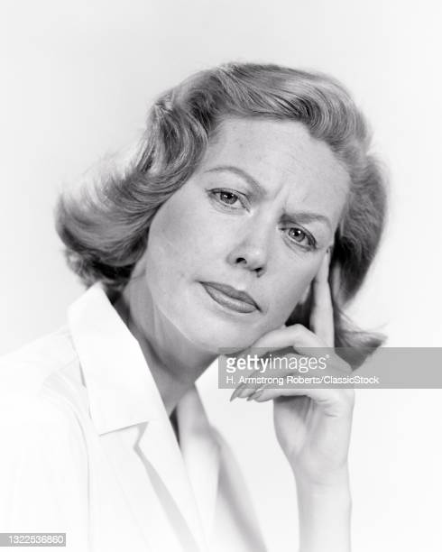 1950s 1960s Woman Concerned Worried Facial Expression Index Finger Pressed To Temple Gesture Looking At Camera.