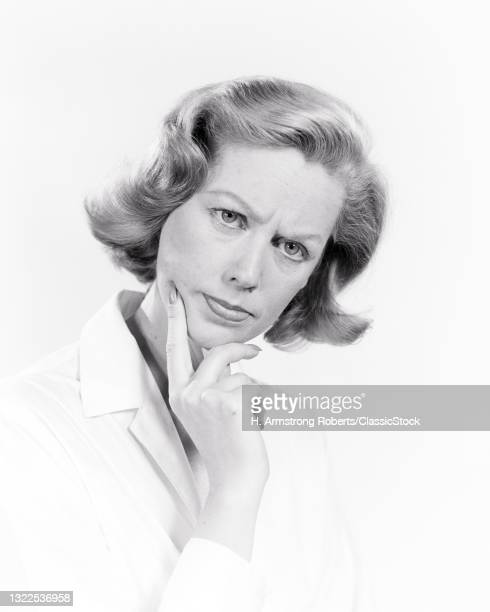 1950s 1960s Woman Concerned Worried Facial Expression Index Finger Pressed To Jaw Gesture Looking At Camera.