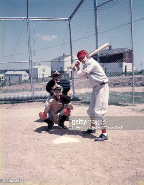 1950s 3 KIDS PLAYING LITTLE LEAGUE BASEBALL AT HOME PLATE A BATTER CATCHER AND UMPIRE