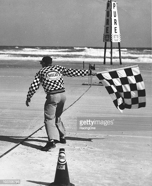 A NASCAR official waves the checkered flag during the Pure Oil Performance trials that were held on Daytona Beach