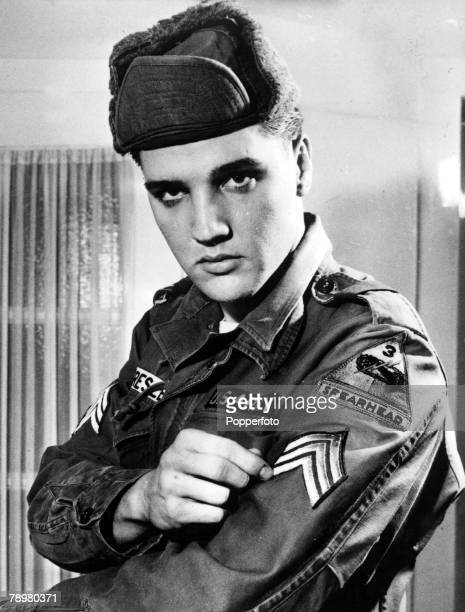 1950s American rock and roll singer and soldier in the US army Elvis Presley admires his new sargeant stripes