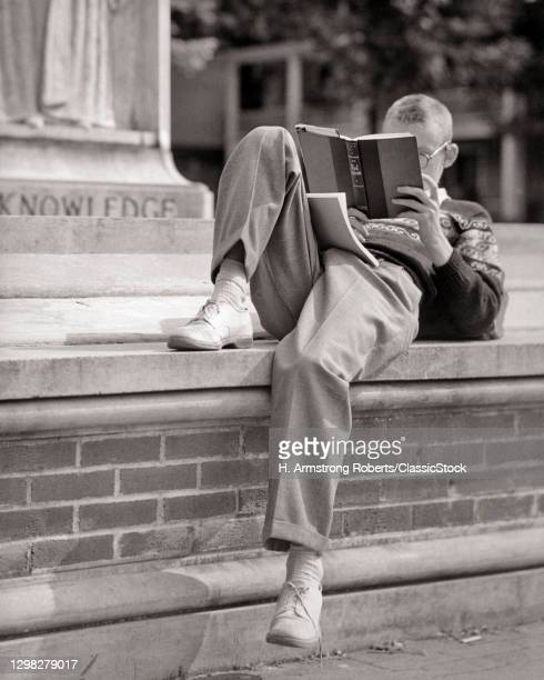1950s Anonymous Blonde Boy Higher Education Student Sitting Reclining On Brick Wall Campus Steps Engrossed In Reading A Book.