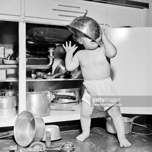 1950s baby girl toddler playing under kitchen sink finding pots pans utensils and wearing colander on head