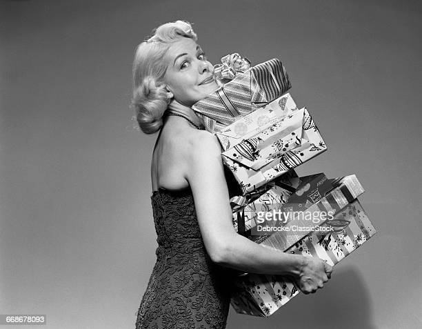 1950s BLOND WOMAN STRAPLESS DRESS CARRYING STACK GIFT WRAPPED PRESENTS CHRISTMAS PACKAGES LOOKING AT CAMERA