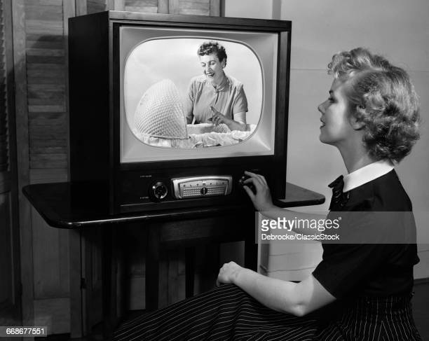 1950s BLONDE WOMAN TURNING DIAL ON TV SET WATCHING PROGRAM ABOUT BABY CHILDCARE