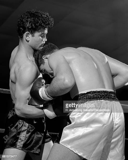 1950s BOXER BEING PUNCHED IN STOMACH DUCKING HEAD DOWN FOR PROTECTION